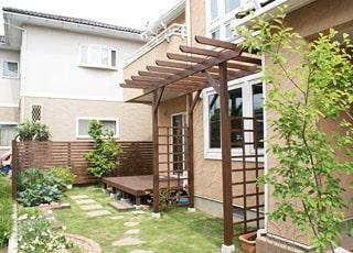 木製物置兼駐輪場とパーゴラがある庭づくり