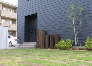 芝と枕木の駐車場が広がるモダン住宅